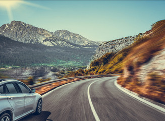 White car on a mountain road. Highway among the mountain scenery. Toned photo. Fototapete