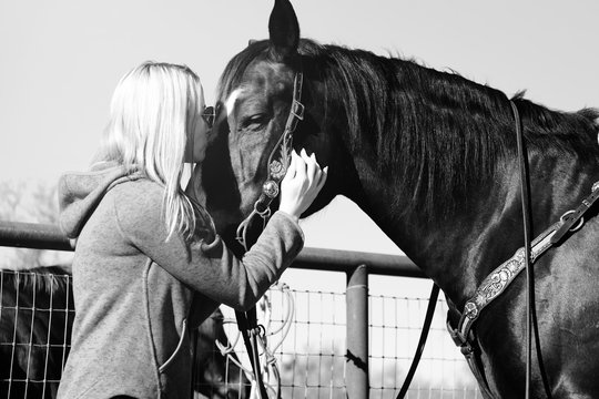Woman with beautiful horse shows love to animal in black and white.  Western lifestyle image.