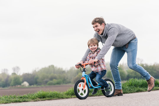 Father teaching son to ride bicycle outdoors