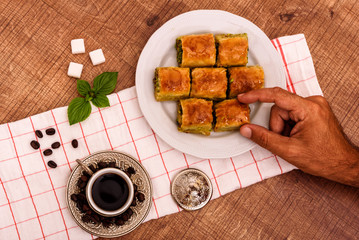 Turkish delights - baklava traditional sweets with turkish coffee, sugar the view from the top on wooden table and white fabric with hand