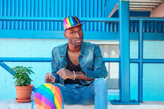 Young man in jean jacket and rainbow baseball cap