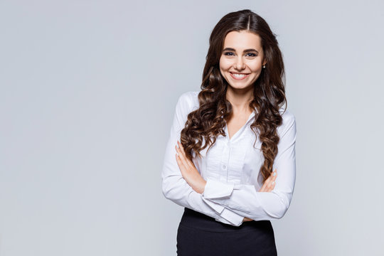 Portrait of young modern business woman in classic suit. Attractive female business leader in smart casual wear with crossed arms. Office worker.