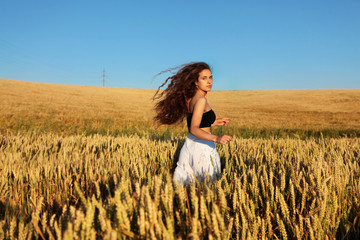 The pretty girl with long hair in stylish white pants and black top running in rye .Stylish girl.Long haired,curly girl.Girl in rye.Summer photos of  in the field. Dynamic photo.Sunset light. Wall mural