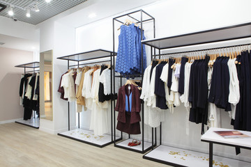 Interior of clothing store .Bright interior.Minimalistic style.Clothes hang on hanger.Trendy colors