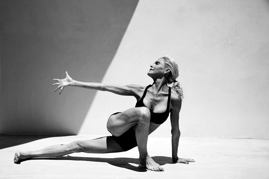Black and white yoga photography. Mature woman practicing advanced yoga postures.