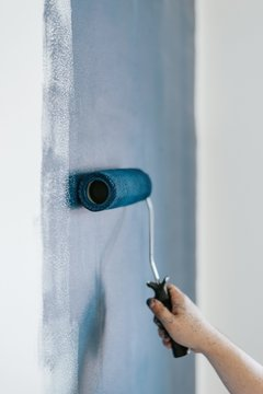 Closeup shot of a female using paint rollers with the color blue