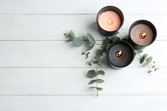 Burning candles and green branches on white wooden table, flat lay. Space for text
