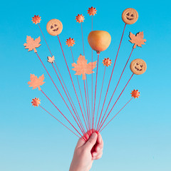 Autumn balloons, creative still life in blue and orange with cookies and autumn leaves on strings in hand