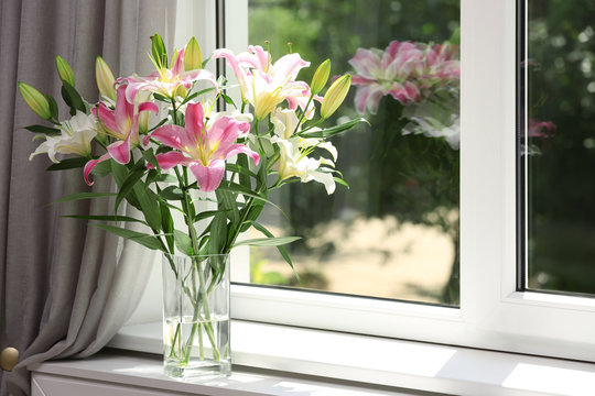 Vase with bouquet of beautiful lilies near window indoors. Space for text