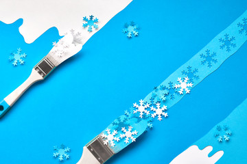 Winter background in blue and white with brushes loaded with paper snowflakes