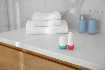 Different deodorants on light countertop in bathroom