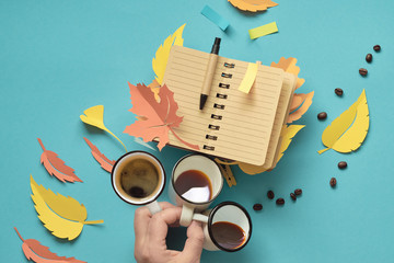 Hand holding three cups of coffee and open notebook with autumn leaves made of paper.