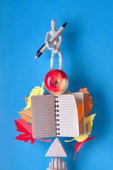 Pyramid with notebook and wooden model man with pen on blue background with Autumn leaves