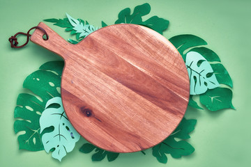 Flat lay, paper tropical leaves around cutting board, copy-space