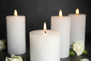 Burning candles and flowers on grey background, closeup