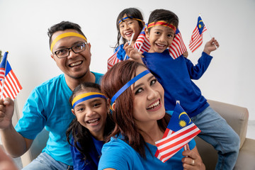 happy malaysia family with kids take selfie for celebrating independence day