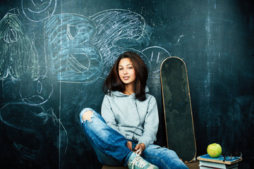 young cute teenage girl in classroom at blackboard seating on table smiling, modern hipster concept Wall mural