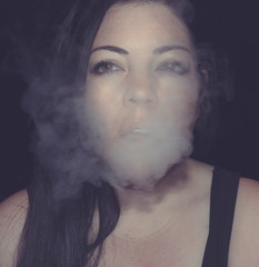 Portrait of a Woman Blowing Vapor From an E-Cigarette