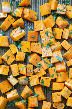 Cubed Butternut Squash on Sheet Pan covered in olive oil, pepper, salt, and parsley, raw vegetable in baking sheet