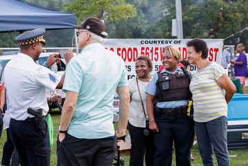Area residents pose for a picture with Chicago Police officer Rashida Young during the National Night Out rally against violence in Chicago