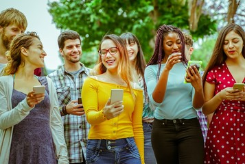 Happy friends using smartphones - Young students people having fun with technology. Friendship and university concept - Image