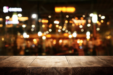 background Image of wooden table in front of abstract blurred restaurant lights Wall mural