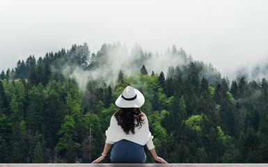 Tuinposter Ontspanning Woman in white hat looking at misty landscape with pine forests in the morning