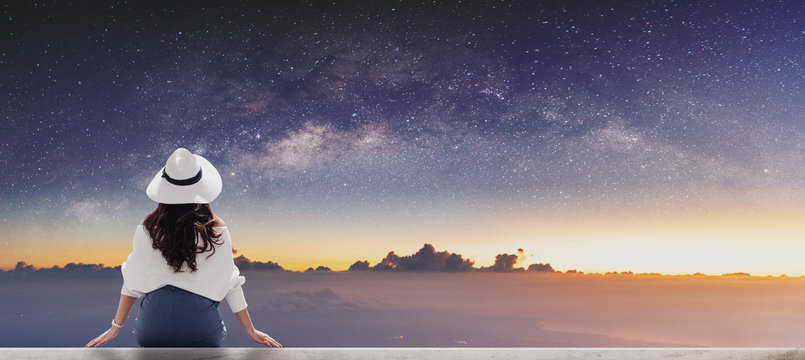Young woman in white hat looking at horizon with sky full of stars at dawn