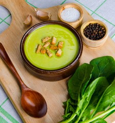 Spinach soup served on wooden board