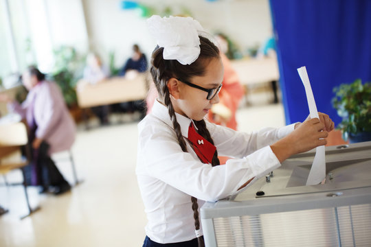 Young pretty girl teenagers in glasses in a white blouse and two bows with pigtails down the ballot in the ballot box in the elections.