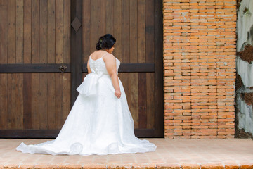 Happy Asian overweight model in beautiful bridal dress or white race wedding dress in many movement