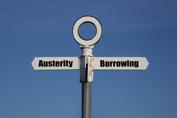 Old road sign with a choice between austerity and borrowing written on it.  Government fiscal policy concept Wall mural
