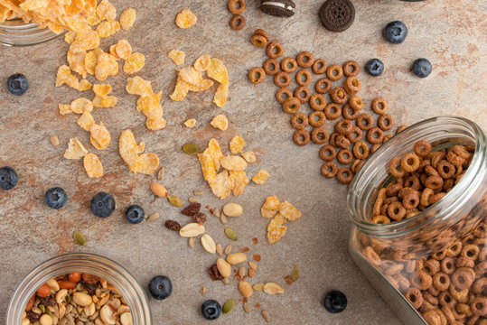 muesli and cereals are scattered with jars of blueberries and sweet cookies on a light background, breakfast background.flat lay? top view