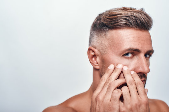 Skin problems. Worried man with a stubble examining his face and looking at camera while standing against grey background