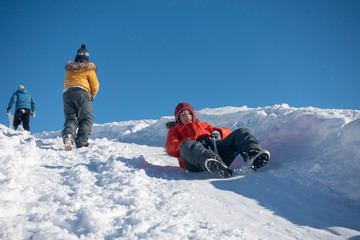 Boy sliding down a hill in the snow in winter