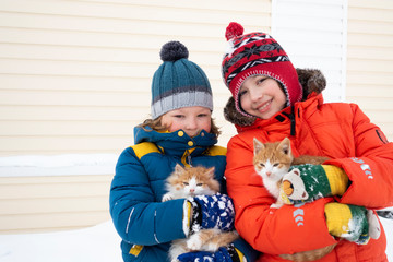 two boys plays with a cat outdoors in winter
