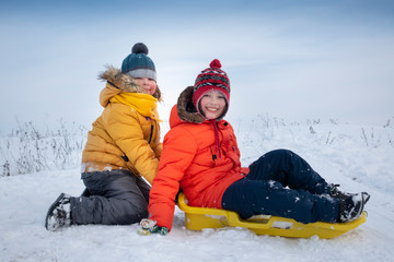 two happy boys on sled and Skis in winter outdoors