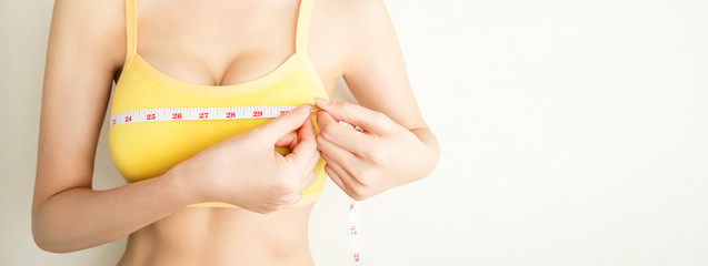 Measure chest. Close up of young beautiful Asian woman measuring size her breast with a tape measure, beauty. Slim sexy female wearing yellow sport bra on gray background. Weight loss concept.