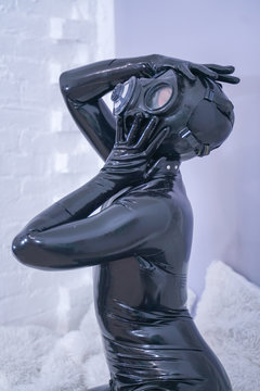Man in the latex rubber black catsuit with gasmask