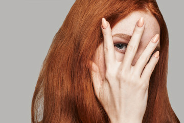 What is there Close up of young and beautiful woman with red silky hair covering face with hand and looking at camera while standing against grey background