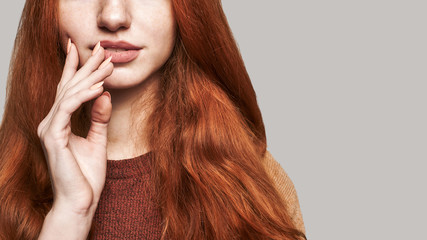Natural beauty. Cropped photo of young and beautiful redhead woman touching her lips and smiling while standing against grey background