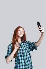 Peace Cute young redhead woman in casual wear making selfie and gesturing while standing against grey background