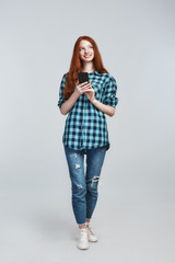 Great news from friend. Young and cute redhead woman in casual wear holding her smart phone and smiling while standing against grey background