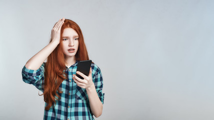 Oh no. Shocked redhead woman in casual wear keeping hand on head and looking at mobile phone while standing against grey background