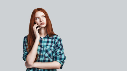 Bad news. Young redhead woman in casual wear is talking on the phone and making sad face while standing against grey background