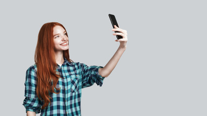 Keep smiling Cute young redhead woman in casual wear making selfie and smiling while standing against grey background