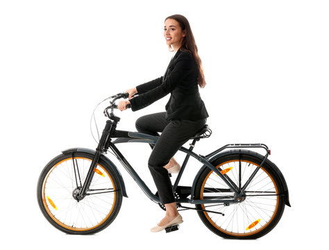 Young businesswoman riding bicycle against white background