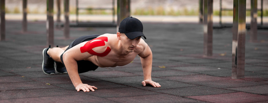 Young European athlete with injury is training outdoors. Kinesiology ( therapeutic, Kinesio, k-tape, KT, physio) tape on shoulder. Rehabilitation and recovery. Push up from the floor.
