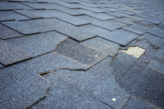 Close up view of bitumen shingles roof damage that needs repair.