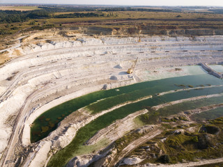 Opencast mining quarry with machinery at work - Aerial view. Industrial Extraction of lime, chalk, calx, caol. View from above